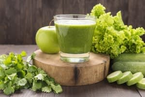 Healthy green vegetables and green fruit smoothie on rustic wood table.